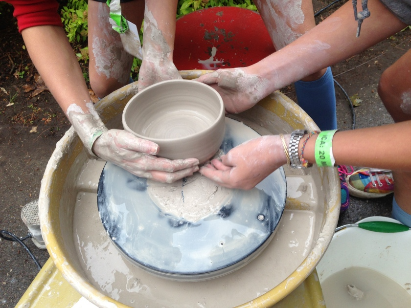 New potters collaborating to remove a bowl from the wheel